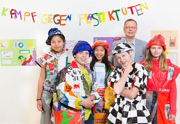 """Herr Schrader (Geschäftsführer Klimapakt, 2. v. r.) mit Schülern der Comenius-Schule, die eine öffentliche """"Plastik-Modenschau"""" inszenieren / Pressebild"""