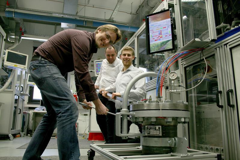 V.l.n.r.: Dr. Ulrich Rost, Jeffrey Roth und Pit Podleschny zeigen auf der Hannover-Messe die Teckenik eines Hochdruck-Elektrolyseur-Prototyps (rechts unten). / Foto: WH/MV