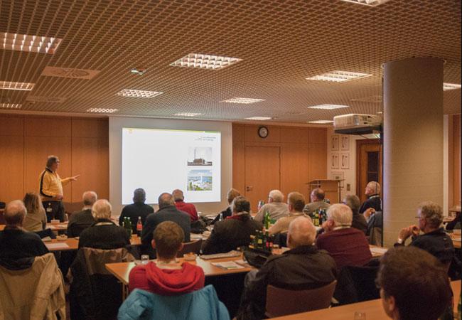 Bildunterschrift: Klaus Dieter Oppermann (links im Bild) erklärt den interessierten Exkursionsteilnehmern die ereignisreiche Entstehungsgeschichte der Stadtwerke Flensburg.