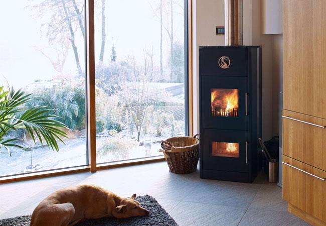 LUVANO Holzvergaser-Kaminofen von LUUMA - Millieu mit Hund / Pressebild