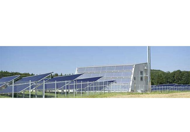 Heizzentrale umgeben von Solarthermiekollektoren. Quelle: solarcomplex AG