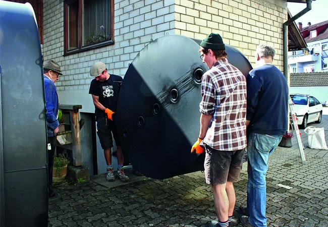 Helfer tragen ein Speichermodul durch einen engen Zugang in den Keller. (© Consolar)