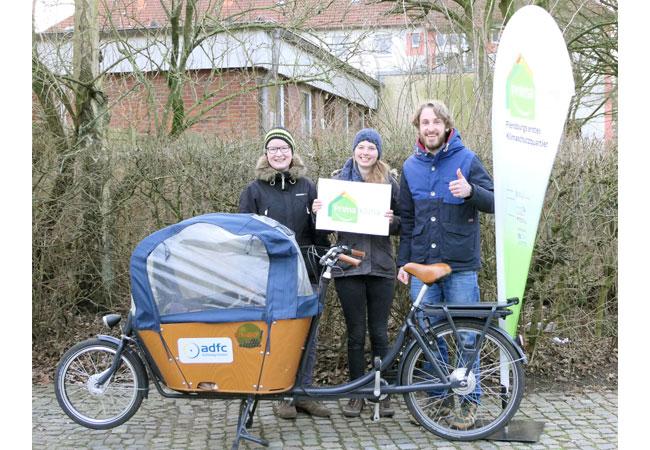 """Annika Jongeling und Henrike Grimm (beide ADFC) sowie Jan Lange (Projektteam """"Prima Klima auf der Rude"""") (v.l.n.r.) freuen sich über das vierwöchige kostenlose Mobilitätsangebot."""