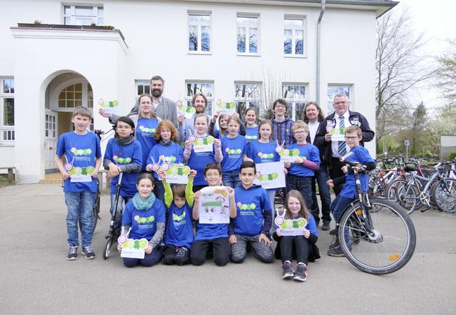 """Bildunterschrift: Bürgermeister und Klimapaktvorsitzender Henning Brüggemann (4.v.l., hinten) nimmt die Herausforderung der Schüler im Rahmen der Aktion """"Ohne Auto zur Schule"""" an."""