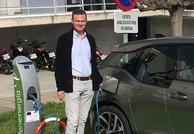 Pressebild: Torben Tuinmann mit Elektroauto an einer Ladesäule auf Mallorca