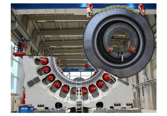 """Im Inneren des """"Windenergie-Prüfstandes"""" rotiert ein überdimensionaler Stahl-Diskus, der die enormen Kräfte aus 64 Axial- und Radialzylindern auf den Prüfling überträgt. Um diese Kräfte unter Kontrolle zu kriegen, sind seine unteren Gehäuseteile mit rund zweihundert M80-Gewindebolzen und einer Vorspannkraft von mehreren Meganewton auf ihren Sockeln fixiert worden."""