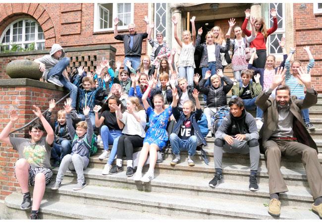 Bildunterschrift: Henning Brüggemann (Klimapakt-Vorsitzender, rechts im Bild) freut sich zusammen mit Akteuren und Schülern über die gelungene Klimaschutz-Kampagne für Flensburger Schüler.