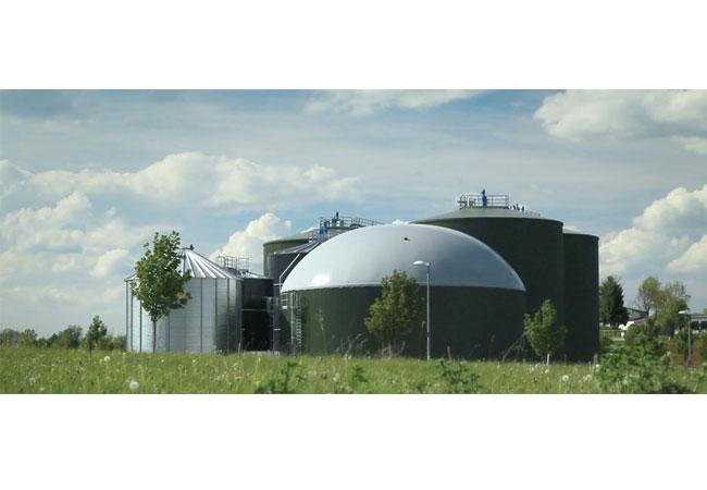 Pressebild: Biogasanlage aus verschiedenen Perspektiven, bei schönem Wetter. Mitarbeiter steigen an Anlage hinauf, arbeiten. Detailaufnahmen der Anlage. Biogasanlage Geislingen, Befüllung des Biofilters für Abluft der Anlage.