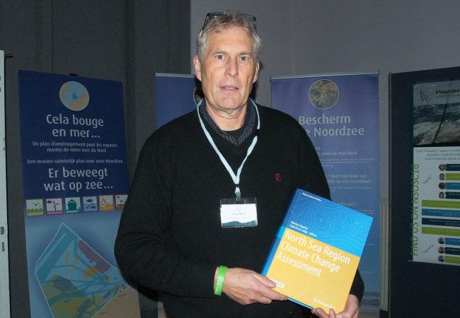 Prof. Dr. Markus Quante mit dem neu erschienenen Buch des NOSCCA Nordsee-Klimaberichts (Foto: RBINS / Frederic Francken)
