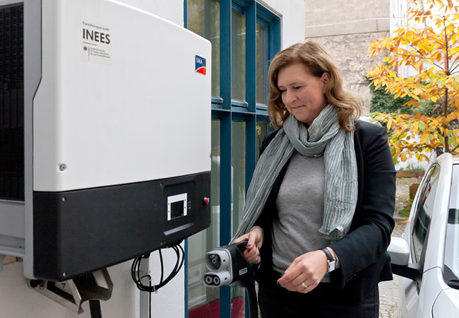 © Foto LichtBlick SE INEES-Projekt von LichtBlick und VW. Frau Dr. Andrea Schirrmacher vom Frauen-Gruenderzentrum in der Anklamer Strasse in ihrem E-Up.