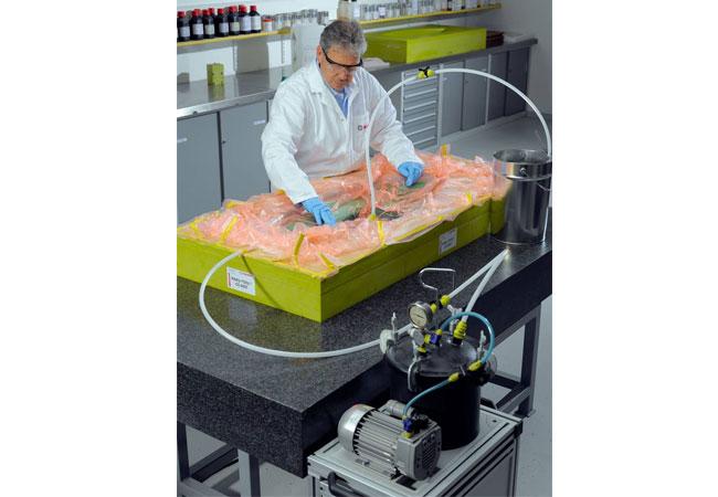 Pressebild: Beim RI-Fertigungsverfahren wird das Faserverbundpaket trocken in die Form eingelegt. Anschließend werden Abreißgewebe, Fließhilfen, Harz- und Vakuumkanäle platziert und die Vakuumfolie abgedichtet. Nachdem der Aufbau unter konstantes Vakuum gesetzt wurde, wird das Epoxid-Infusion-System durch den bestehenden Druckunterschied injiziert und das Faserverbundpaket imprägniert.