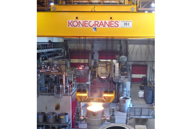 Pressebild: In sicherer Entfernung: Per Funk steuert der Kranführer den neuen Gießereikran von Konecranes mit 70 Tonnen Tragkraft an der Pfannentraverse und dirigiert zugleich die Gusspfannen mit feuerflüssiger Masse.
